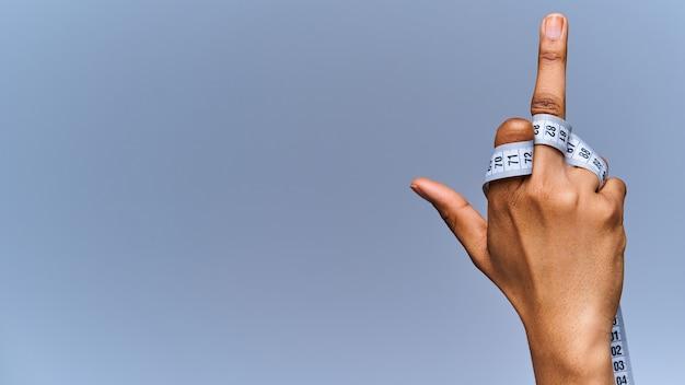 Bliska żeńska ręka z elastycznym miernikiem z podniesionym środkowym palcem - zły znak. pojęcie diety