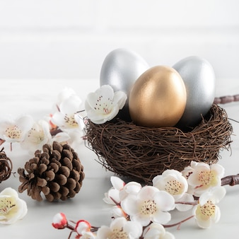 Bliska złote i srebrne pisanki w gnieździe z kwiatem białej śliwki na jasny biały drewniany stół.