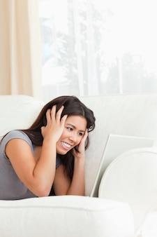 Bliska, zły kobieta, leżąc na kanapie z notebooka