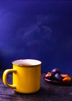 Bliska żółta filiżanka herbaty na drewnianym stojaku, ciemnoniebieskie tło, owoce na małym talerzu ceramicznym