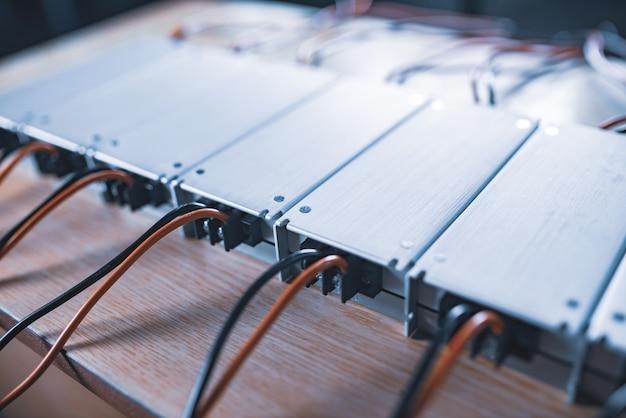 Bliski metalowy zasilacz ac-dc z przewodami leżą na drewnianym stole w oczekiwaniu na dalszą instalację w produkcji urządzeń dla wyspecjalizowanych przedsiębiorstw. koncepcja sprzętu high-tech