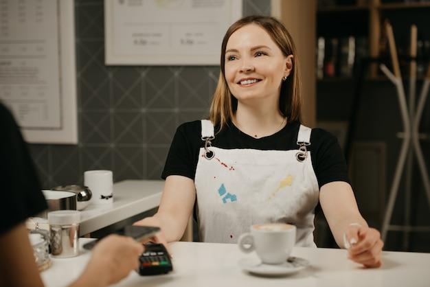 Bliski portret kobiety-baristy, która z uśmiechem podaje klientowi terminal do zapłaty. kobieta płaci za filiżankę latte ze smartfonem za pomocą zbliżeniowej technologii pay pass w kawiarni.