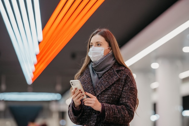 Bliski portret kobiety w medycznej masce na twarz siedzi na stacji metra ze smartfonem i czeka na pociąg. dziewczyna w masce chirurgicznej trzyma dystans społeczny w metrze.