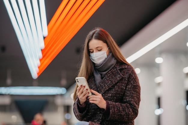 Bliski portret kobiety w medycznej masce na twarz siedzi na stacji metra ze smartfonem i czyta wiadomości. dziewczyna w masce chirurgicznej trzyma dystans społeczny w metrze.
