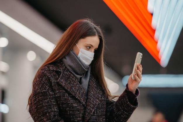 Bliski portret kobiety w medycznej masce na twarz siedzi na stacji metra ze smartfonem i robi selfie. dziewczyna w masce chirurgicznej trzyma dystans społeczny w metrze