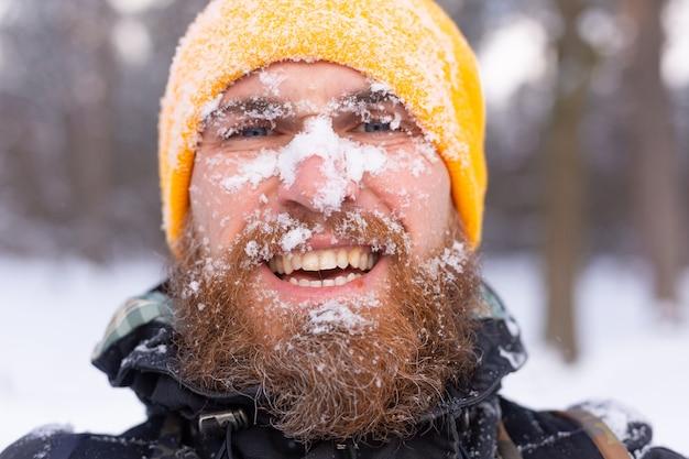 Bliski portret mężczyzny z brodą, cała twarz na śniegu, w zaśnieżonym lesie