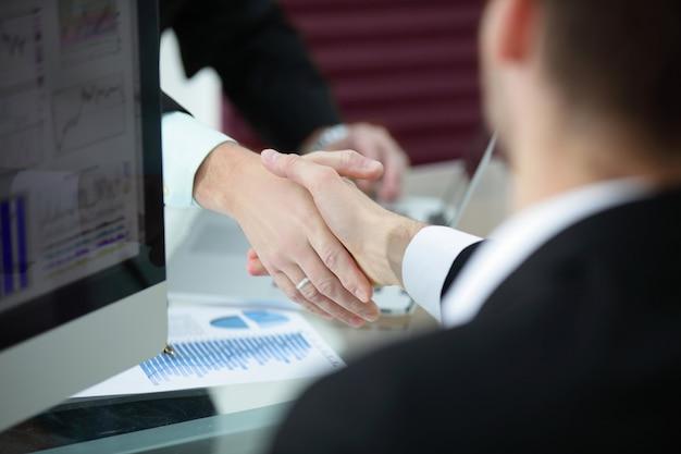 Bliski uścisk dłoni partnerów biznesowych nad biurkiem