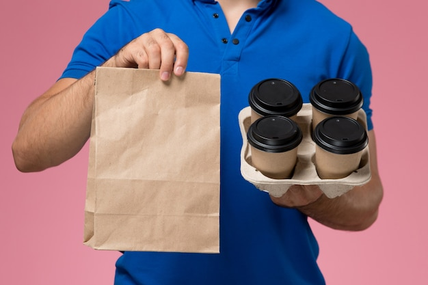 Bliski widok z przodu kurier męski w niebieskim mundurze, trzymający dostawy filiżanek kawy, opakowania żywności na różowym, jednolitym dostawie pracy serwisowej