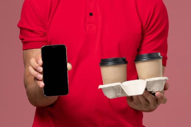 Bliski widok z przodu kurier w czerwonym mundurze trzymający brązowe filiżanki z kawą i telefon na jasnoróżowej ścianie
