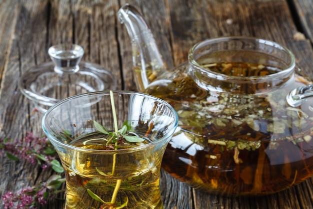 Bliski wschód czarna herbata z tymiankiem, etnicznym szkłem i szklanym czajnikiem, rocznika drewna tło