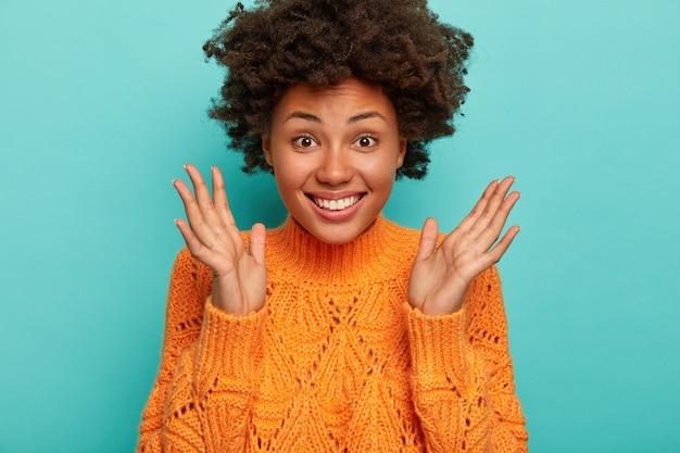 Bliskie ujęcie radosnej, kręconej kobiety wyraża entuzjazm i radość, trzyma dłonie uniesione, szeroko się uśmiecha, nosi jasny zimowy sweter, lubi zabawną noc z przyjaciółmi, na białym tle na niebieskim tle
