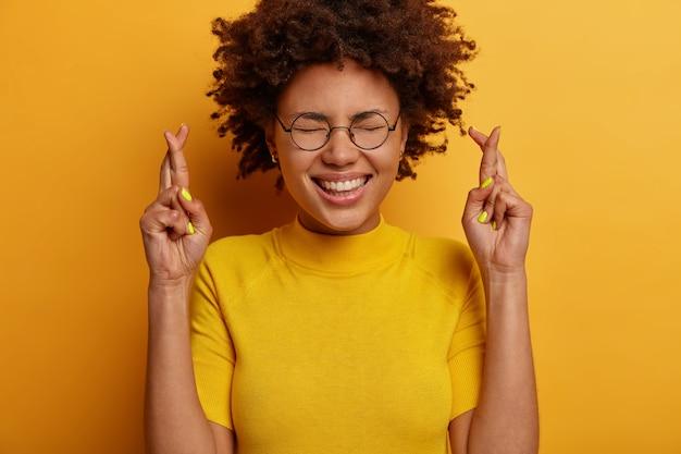Bliskie ujęcie wesołej etnicznej dziewczyny trzyma wiarę, krzyżuje palce, błaga o dobre wieści, uśmiecha się szeroko, czeka na coś ważnego, czeka na pozytywny wynik, nosi okulary i koszulkę
