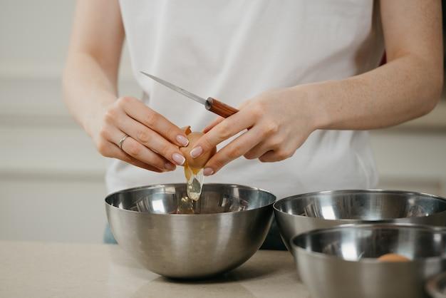 Bliskie zdjęcie dłoni dziewczyny, która rozbija jajko z ekologicznej farmy, trzymając nóż nad miską na zupę ze stali nierdzewnej w kuchni.