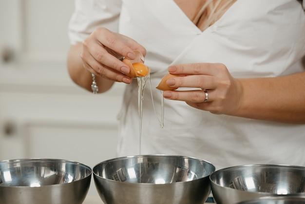 Bliskie zdjęcie dłoni kucharki, która oddziela żółtko od białka jaja nad miską na zupę ze stali nierdzewnej w kuchni.