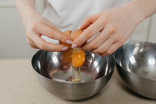 Bliskie zdjęcie dłoni młodej kobiety, która rozbija jajko ekologiczne nad miską na zupę ze stali nierdzewnej w kuchni.