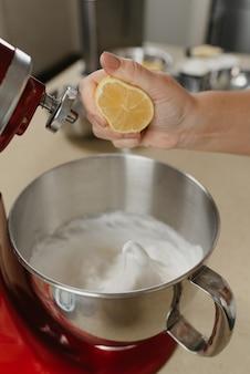 Bliskie zdjęcie dłoni młodej kobiety miażdżącej sok z cytryny na bezę mieszaną w misce ze stali nierdzewnej w kuchni