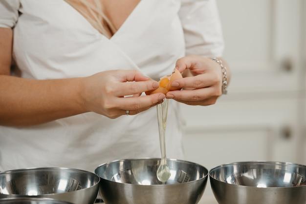 Bliskie zdjęcie dłoni młodej kobiety oddzielającej żółtko od białka jaja nad miską ze stali nierdzewnej w kuchni