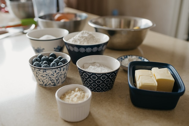 Bliskie zdjęcie małego stosu skrobi w spodeczku w pobliżu, masła i jagód w filiżankach.