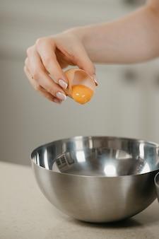 Bliskie zdjęcie ręki młodej kobiety, która spada żółtko jaja ekologicznego do miski ze stali nierdzewnej na zupę w kuchni.