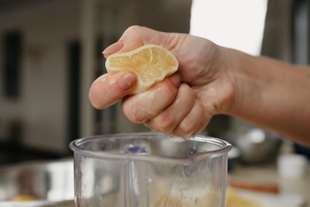 Bliskie zdjęcie z boku dłoni młodej kobiety miażdżącej ręką sok z cytryny do kubka blendera w kuchni