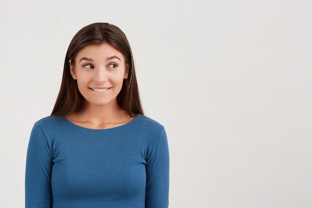 Bliskość szczęśliwej, figlarnej młodej kobiety z długimi włosami nosi granatowy longsleeve gryząc wargę i pokazując znak ciszy odizolowany na białej ścianie