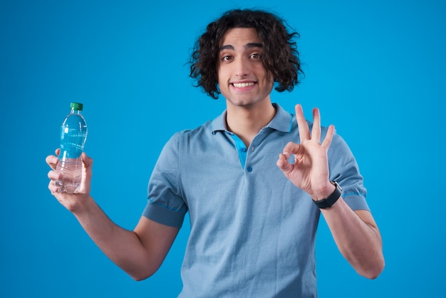 Bliskowschodni mężczyzna pozuje z wodą odizolowywającą.