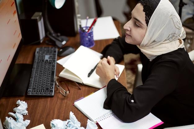 Bliskowschodnia przedsiębiorczyni. zajęta arabska bizneswoman. kobieta w tradycyjnej arabskiej odzieży hidżab lub abaya pracuje na komputerze