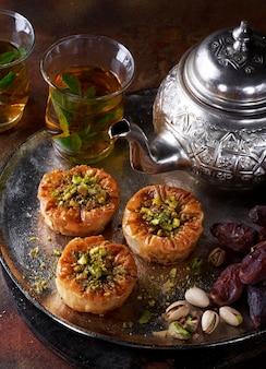 Bliskowschodnie, arabskie słodkie gniazda filo baklava, różne przysmaki, suszone daktyle, pistacje, miód na ciemnej zardzewiałej ścianie. selektywna ostrość. ramadan, koncepcja id.