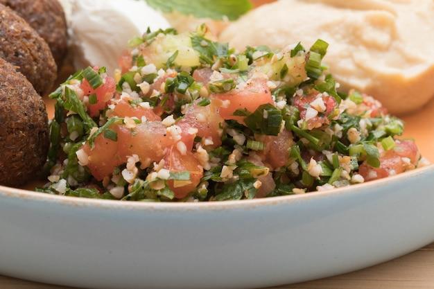Bliskowschodnie jedzenie. arabskie jedzenie. pyszne tabouleh na pięknym rustykalnym talerzu.