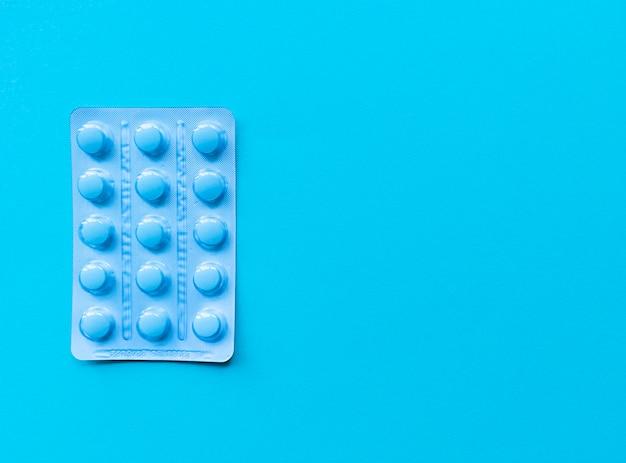 Blister niebieskich tabletek na niebieskim tle. monochromatyczne proste mieszkanie z pastelową teksturą z miejscem na kopię. pojęcie medyczne.