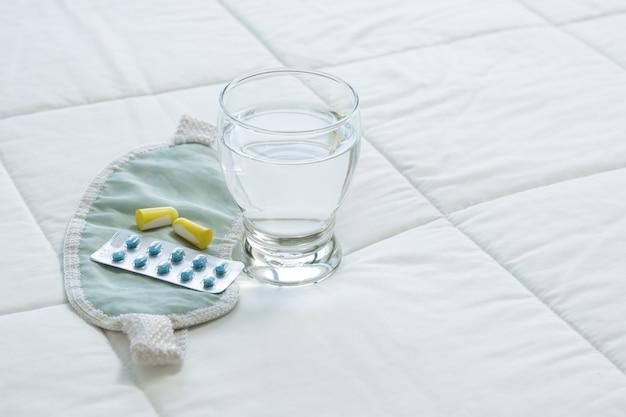 Blister tabletek nasennych, opaski i szklanki wody