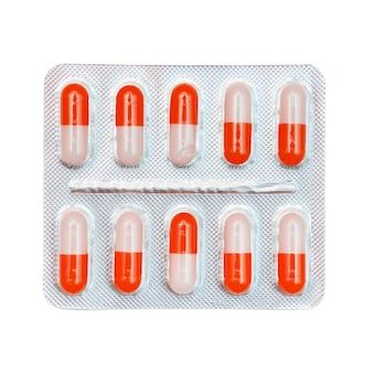 Blister zawierający czerwono-białe kapsułki