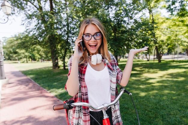 Blithesome blondynka śmiejąca się podczas jazdy na rowerze. zewnętrzne zdjęcie ekstatycznej białej kobiety w słuchawkach.