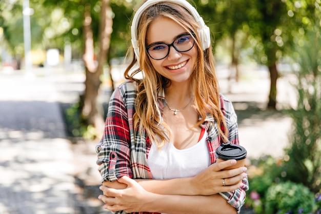 Blithesome dziewczyna w białych słuchawkach uśmiechając się do natury. odkryty strzał niesamowitej modelki z filiżanką kawy słuchając muzyki.