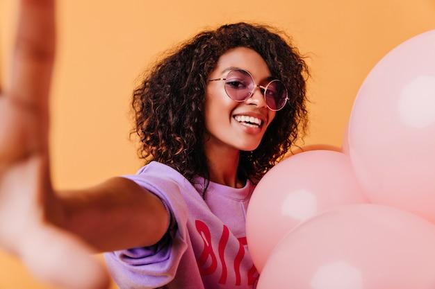 Blithesome girl z falującymi włosami pozuje z podekscytowaniem na pomarańczowo. jocund afrykańska kobieta robi selfie z balonów helem.