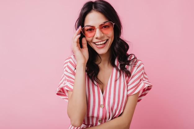 Blithesome kaukaski kobieta z ładnym uśmiechem dotykając jej okulary. portret śmieszne dziewczyna brunetka na białym tle.