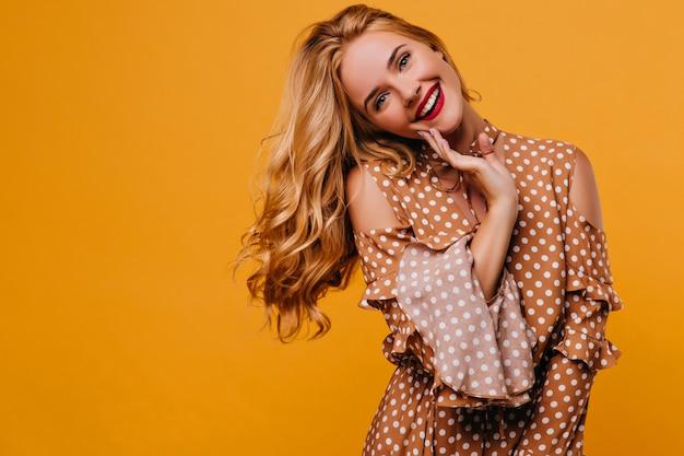 Blithesome kaukaski kobieta z modnym makijażem pozuje z uśmiechem. kryty strzał z uroczą białą damą w ubraniach vintage.