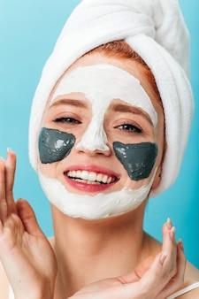 Blithesome młoda kobieta robi leczenie uzdrowiskowe. studio strzałów z roześmianą dziewczyną z ręcznikiem i maską.