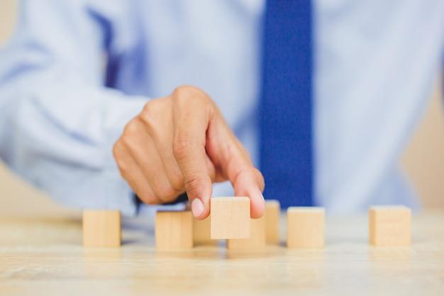 Bliżej rąk biznesmenów, układając drewniane klocki w kroki