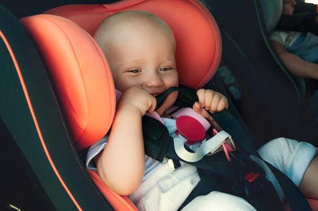 Bliźniacy chłopiec i dziewczynka w fotelikach dziecięcych w samochodzie. bezpieczny transport dla niemowląt. dzieci do roku.