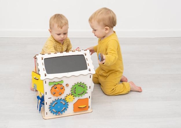 Bliźniacze chłopcy bawią się zabawką