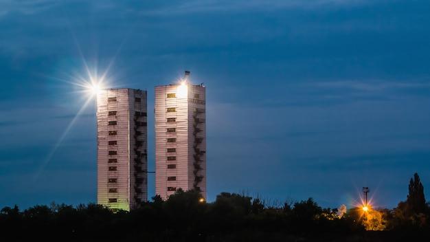 Bliźniacze wieże kopalni gvardeiskaya o zmierzchu z ogólnymi światłami