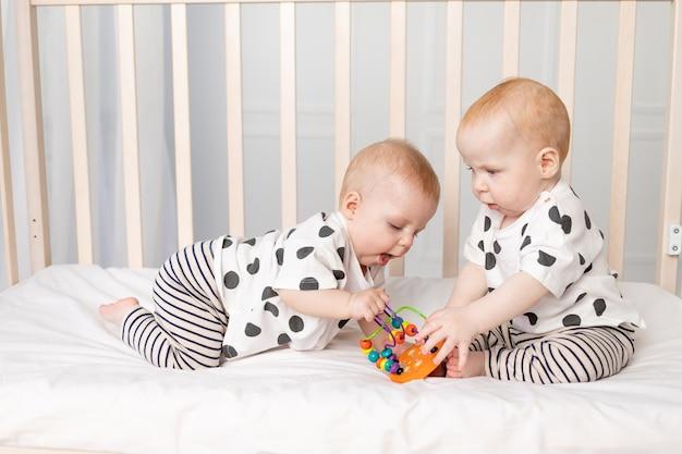 Bliźniaczki bawią się w łóżeczku, wczesny rozwój dzieci do roku