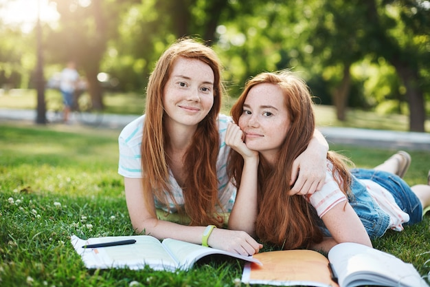 Bliźniaczki ginger przygotowują się do egzaminów na świeżym powietrzu w miejskim parku. nauka jest o wiele lepsza z najlepszym przyjacielem. koncepcja badań i wiedzy.
