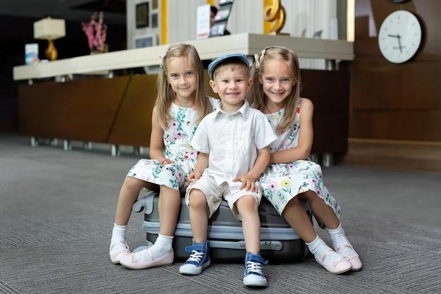 Bliźniaczki i brat siedzą na walizce w hotelu.