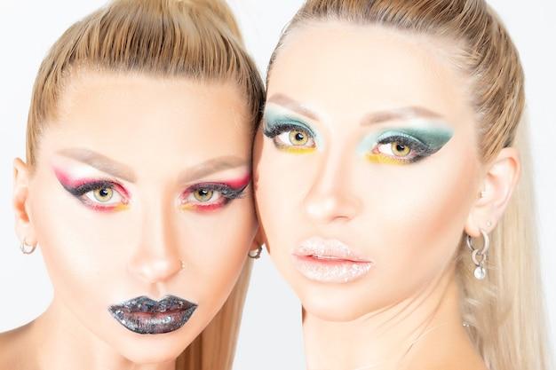 Bliźniaczki mody z jasnym makijażem pozowania