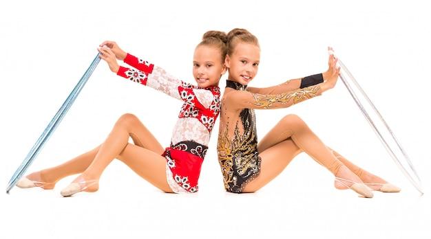 Bliźniaczki robią ćwiczenia gimnastyczne z obręczy.