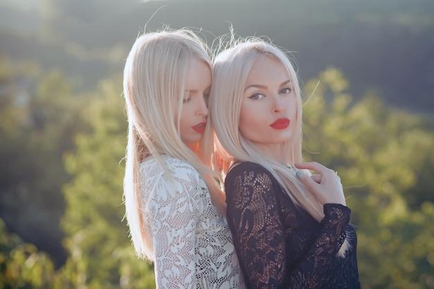 Bliźniaczki siostry pozują na słonecznym naturalnym krajobrazie