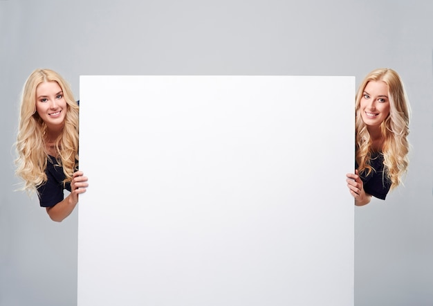 Bliźniaki po obu stronach pustego plakatu