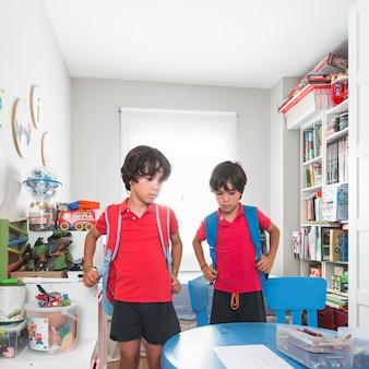 Bliźniaki z plecakami stojącymi w pokoju przedszkolnym